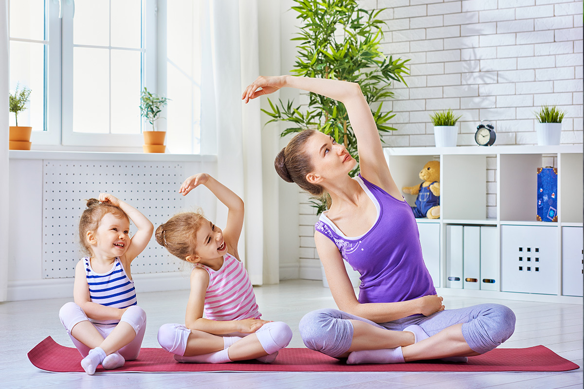 mother doing yoga with her young daughters