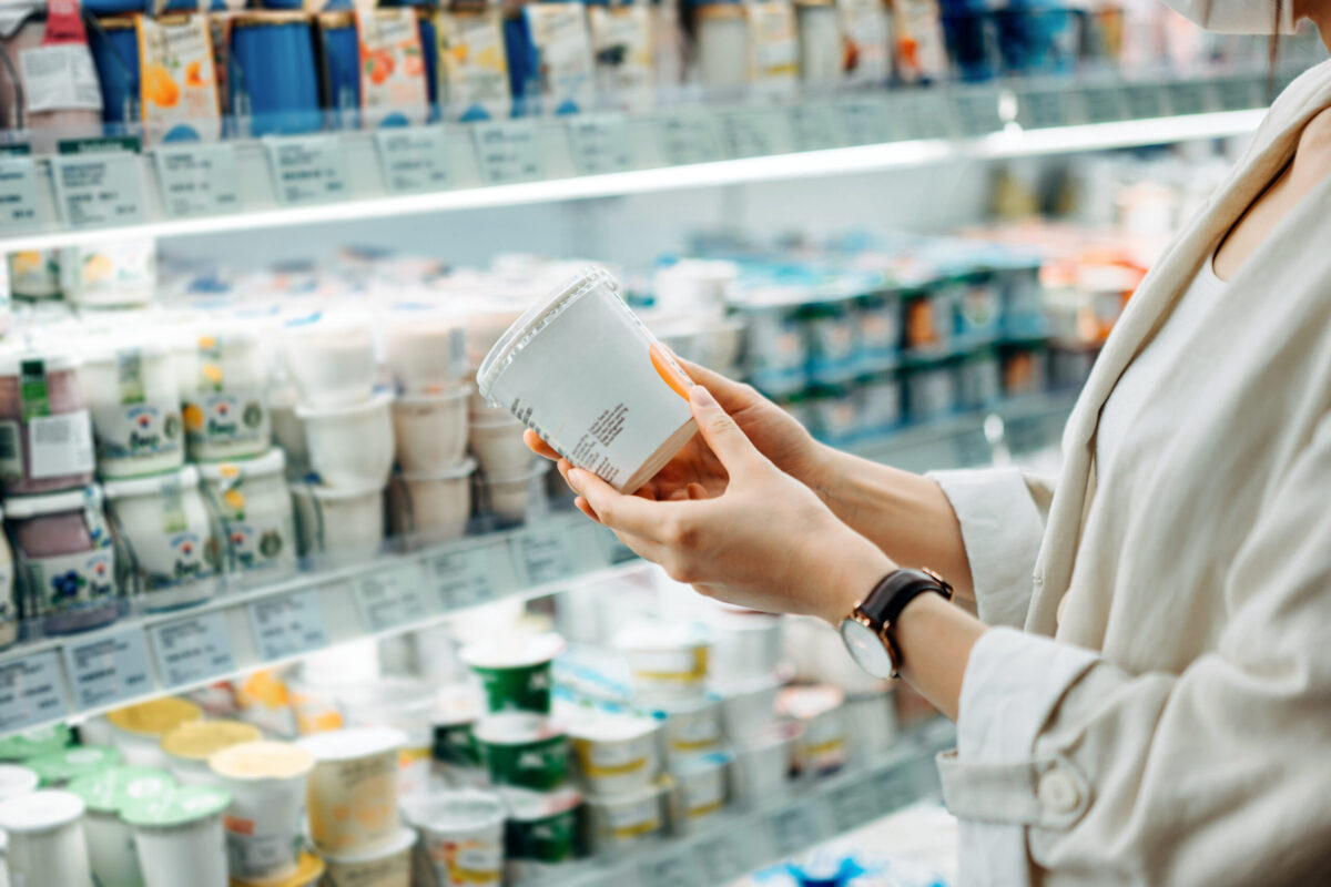 Cropped shot of young woman shopping in the dairy section of a supermarket. She is reading the nutrition label on a container of fresh organic healthy natural yoghurt