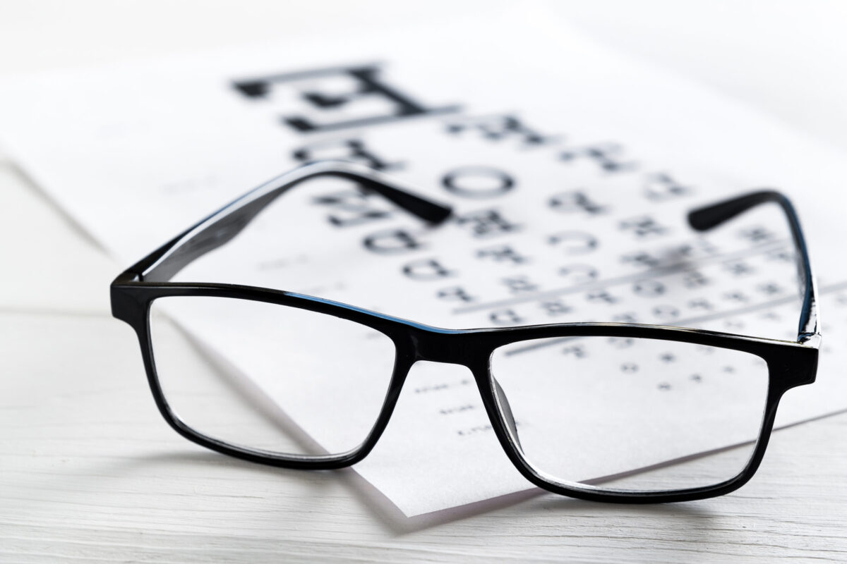 Transparent black modern fashion glasses on the Snellen vision test chart. Ophthalmology, visual acuity testing, treatment and prevention of eye diseases. The concept of poor vision, blindness, going to an ophthalmologist.